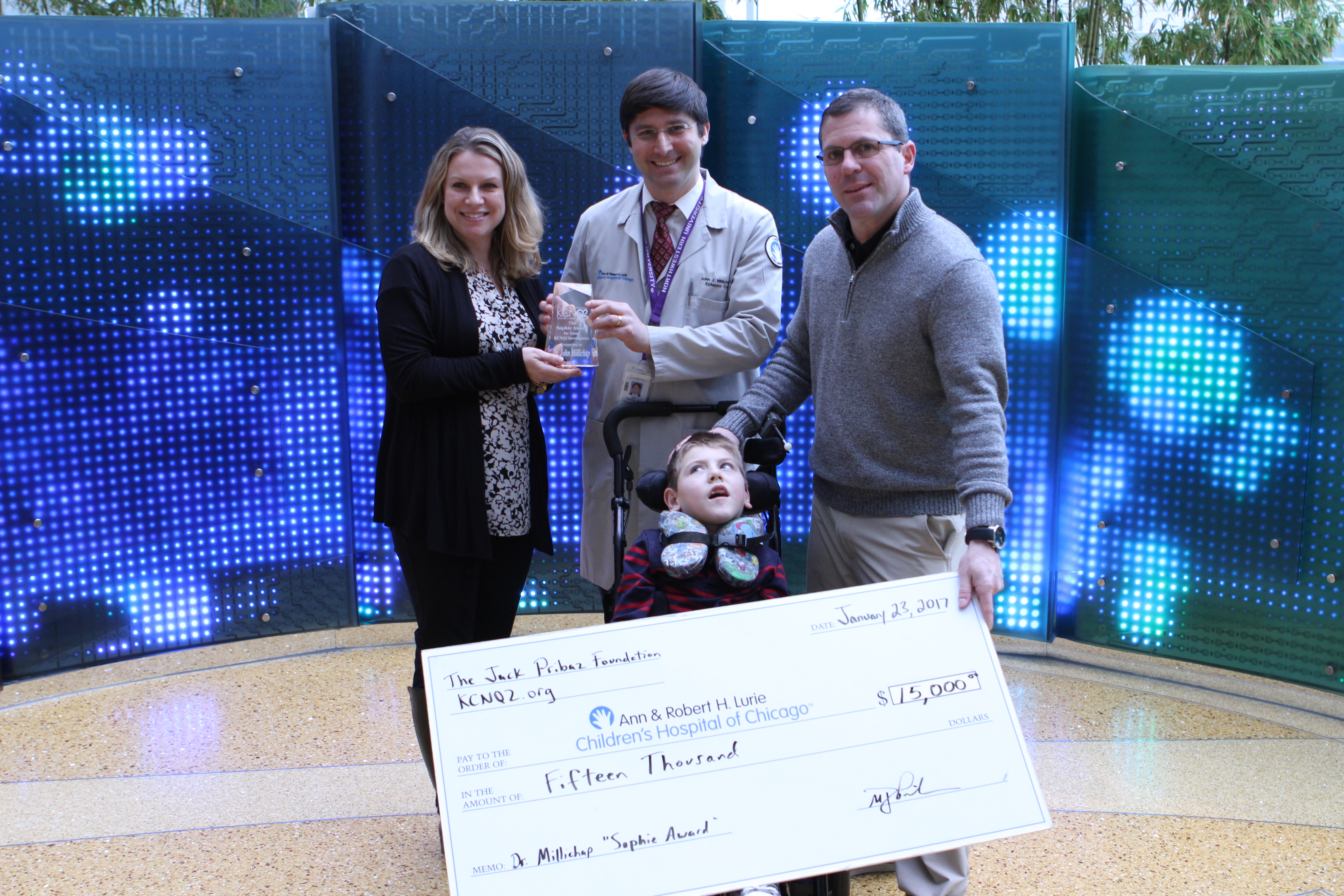 Liz Pribaz presents Dr. John Millichap with the first ever Sophie Award for Young KCNQ2 Investigators on January 23, 2016, at Lurie Childrens' Hospital in Chicago. Mike Pribaz and son Jack hand off the big check.